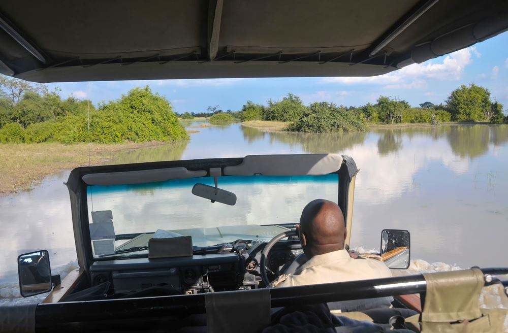 A safari vehicle driving through water in the Okavango Delta in Botswana